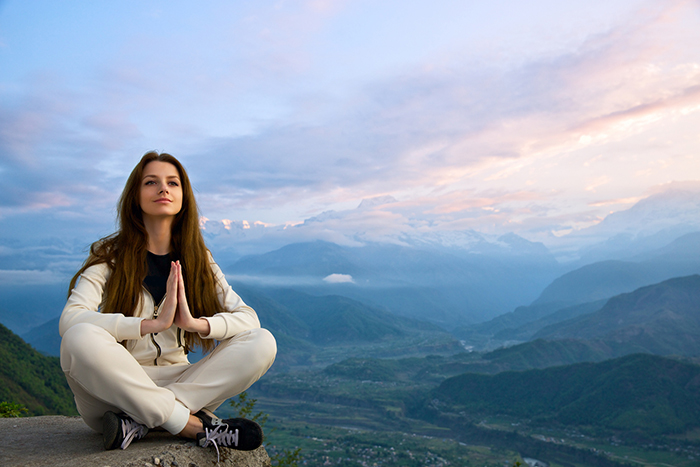 Young beautiful woman meditating in The Himalayas at sunrise
